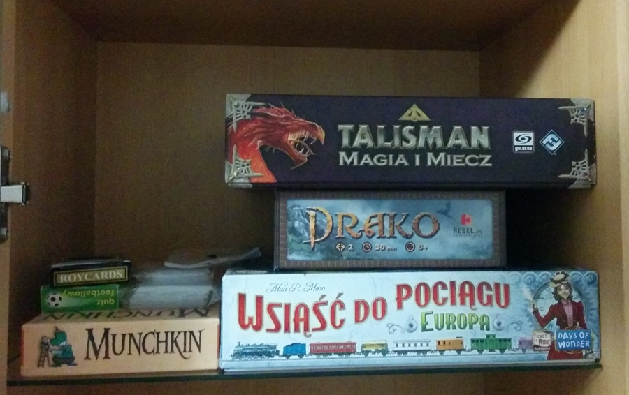 Photo of 4 board games and decks of cards on a shelf